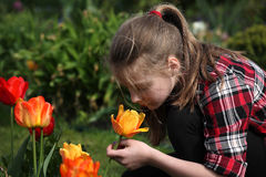 Flicka som luktar blommor i trädgården Royaltyfri Foto