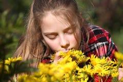 Flicka som luktar blommor i trädgården Royaltyfri Fotografi