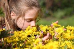 Flicka som luktar blommor i trädgården Arkivbilder