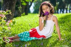 Flicka som luktar blommor som ler på kameran Arkivbild