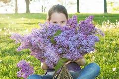 Flicka som luktar buketten av lila blommor Royaltyfri Foto