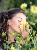 Flicka som luktar en blomma royaltyfria bilder