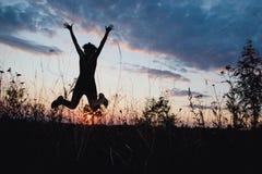 Flicka som lyckligt hoppar i solnedgångljus Sommar natur som är utomhus-, frihet, framgång, lyckabegrepp royaltyfria foton