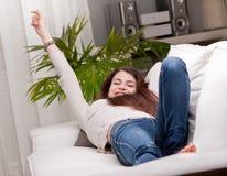 Flicka som lyckligt vaknar upp på hennes soffa Arkivbild