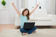 Flicka som lyfter armar med bärbara datorn Royaltyfri Foto