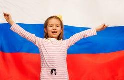 Flicka som lyfter henne händer upp mot flagga av Ryssland arkivbilder