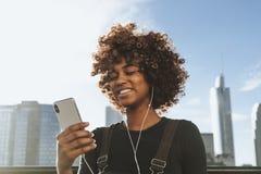 Flicka som lyssnar till musik från hennes telefon arkivbild