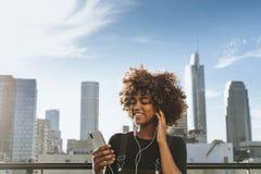 Flicka som lyssnar till musik från hennes telefon royaltyfria foton