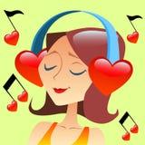 Flicka som lyssnar till musik med hörlurar i form av en röd hea Royaltyfri Foto