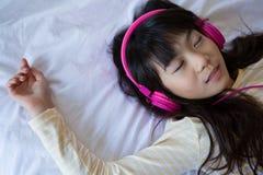 Flicka som lyssnar till musik, medan koppla av på säng Fotografering för Bildbyråer