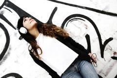 Flicka som lyssnar till musik, medan luta på en vägg Arkivbild