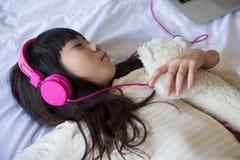 Flicka som lyssnar till musik, medan vila på säng Arkivfoto