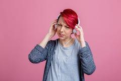 Flicka som lyssnar till musik på hörlurar, som hon inte gillar royaltyfri bild