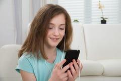 Flicka som lyssnar till musik på mobiltelefonen Arkivfoto