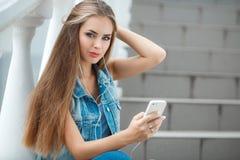 Flicka som lyssnar till musik som sitter på momenten royaltyfria foton