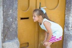 Flicka som lyssnar till och med den orange dörren fotografering för bildbyråer