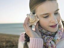 Flicka som lyssnar till snäckskalet på stranden royaltyfri bild