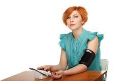 Flicka som mäter sig tryck med en tonometer som isoleras på whi Royaltyfria Foton