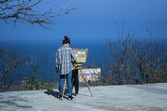 Flicka som målar en bild av ett blått hav royaltyfria foton