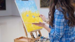 Flicka som målar en bild genom att använda blåttfärg lager videofilmer