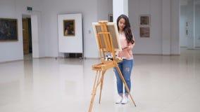 Flicka som målar en bild i konstgalleri stock video