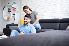 Flicka som masserar pojkvännen på Sofa At Home Arkivbilder