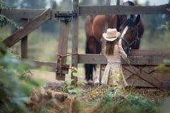 Flicka som matar henne hästen Royaltyfria Bilder