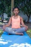 Flicka som mediterar i gård Royaltyfri Fotografi