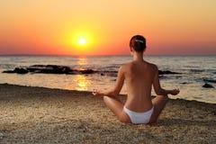 Flicka som mediterar i soluppgång fotografering för bildbyråer