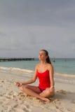Flicka som mediterar på stranden Arkivbild