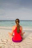 Flicka som mediterar på stranden Royaltyfria Foton