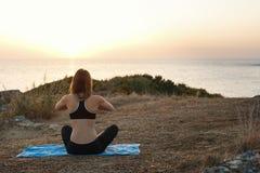 Flicka som mediterar på stranden på solnedgången Fotografering för Bildbyråer