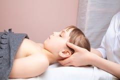Flicka som mottar osteopathic behandling av hennes huvud arkivbild