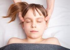 Flicka som mottar osteopathic behandling av hennes huvud Royaltyfri Foto