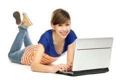 Flicka som ner ligger med bärbar dator Fotografering för Bildbyråer
