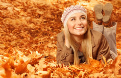 Flicka som ner ligger på höstliga leaves Arkivbilder
