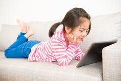 Flicka som ner ligger på soffan genom att använda den digitala minnestavlan Arkivbild