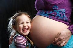 Flicka som omfamnar den gravida modern arkivbilder