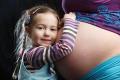 Flicka som omfamnar den gravida modern royaltyfria foton