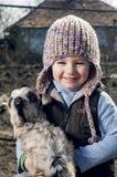 Flicka som omfamnar en goatling. Arkivbilder