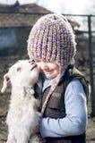 Flicka som omfamnar en goatling. Fotografering för Bildbyråer