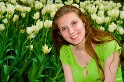 Flicka som omges av blommande tulpan royaltyfri fotografi
