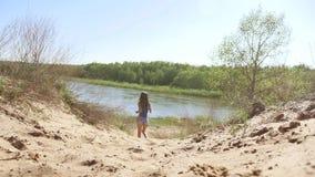 Flicka som omkring kör i naturen på sanden kvinnasport i natur nära livsstil floden stock video