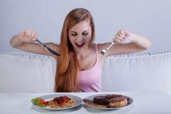 Flicka som på en gång äter mycket mat royaltyfria foton