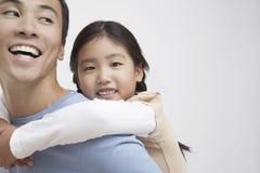 Flicka som på ryggen tycker om ritt på fader arkivfoton