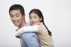 Flicka som på ryggen tycker om ritt på fader royaltyfri bild