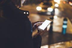 Flicka som pekar fingret på skärmsmartphonen på bakgrundsbokehljus i atmosfärisk stadsgata för natt, använda för bloggerhipsterfl royaltyfri fotografi