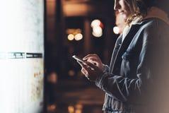 Flicka som pekar fingret på skärmsmartphonen på den ljusa asken för bakgrund i den atmosfäriska stadsöversikten för natt, hipster Arkivfoto