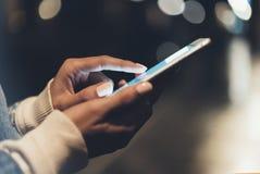 Flicka som pekar fingret på skärmsmartphonen på ljus för färg för bakgrundsbelysningbokeh i atmosfärisk stad för natt royaltyfri fotografi