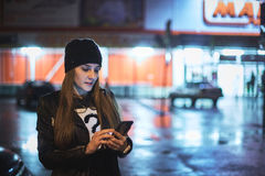 Flicka som pekar fingret på skärmsmartphonen på ljus för färg för bakgrundsbelysningbokeh i atmosfärisk stad för natt Royaltyfri Bild